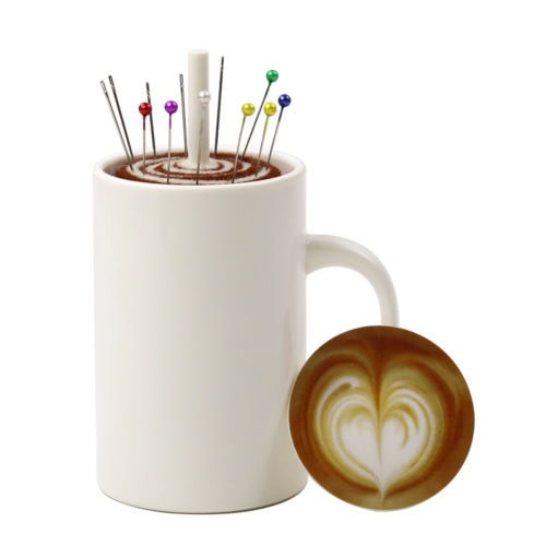 Novelty Coffee Cup Pin Cushion. This adorable novelty pin cushion is operated by pressing down on the 'coffee' at the top of the coffee cup. The pin cushion then pops up from underneath.